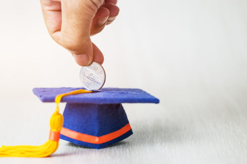 Student putting money into a savings box to help with financing you medical degree abroad