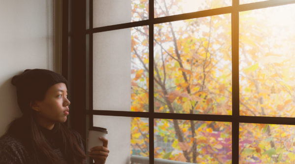 student looking outside whilst feeling homesick because she is studying medicine abroad
